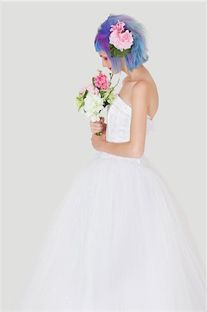 Side view of young woman in wedding dress with dyed hair against gray background Stock Photo - Premium Royalty-Free, Code: 693-06378828