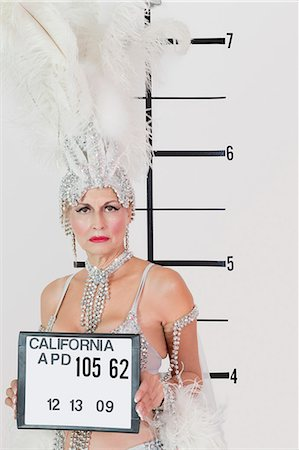 Mug shot of senior showgirl holding plaque Stock Photo - Premium Royalty-Free, Code: 693-06378834
