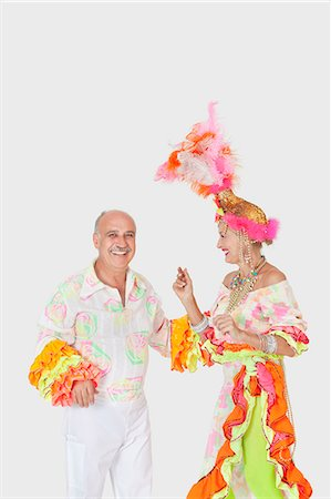 Happy senior dancing couple in Brazilian outfits dancing over gray background Stock Photo - Premium Royalty-Free, Code: 693-06378876