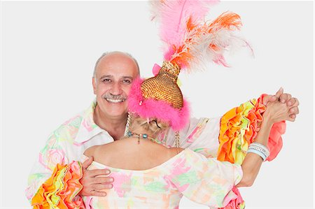Portrait of senior couple in Brazilian outfits dancing over gray background Stock Photo - Premium Royalty-Free, Code: 693-06378878