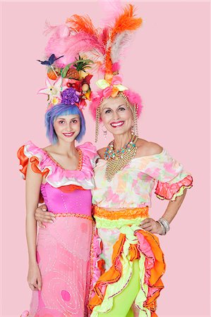 Portrait of happy young and senior women in Brazilian outfits over pink background Stock Photo - Premium Royalty-Free, Code: 693-06378871