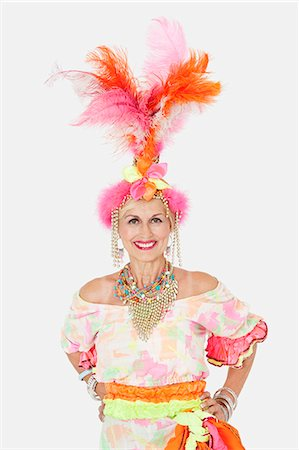 Portrait of happy senior woman in Brazilian outfit over gray background Stock Photo - Premium Royalty-Free, Code: 693-06378872
