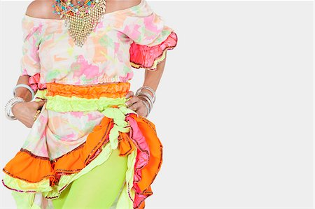 Midsection of senior woman in Brazilian costume over gray background Stock Photo - Premium Royalty-Free, Code: 693-06378873