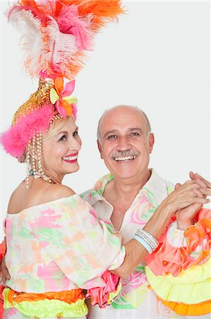Portrait of senior couple in Brazilian outfits dancing over gray background Stock Photo - Premium Royalty-Free, Code: 693-06378880