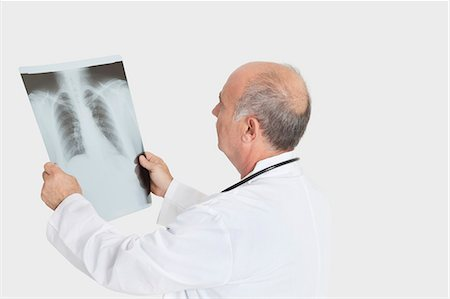Senior male doctor examining medical radiograph over gray background Stock Photo - Premium Royalty-Free, Code: 693-06378909