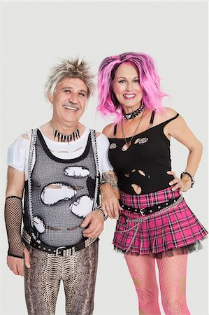 Portrait of senior punk couple standing with arm in arm over gray background Stock Photo - Premium Royalty-Free, Code: 693-06378971