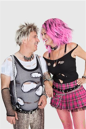 Happy senior punk couple looking at each other over gray background Stock Photo - Premium Royalty-Free, Code: 693-06378972