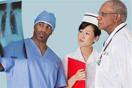 Multi ethnic doctors examining x-ray report over light blue background Stock Photo - Premium Royalty-Free, Code: 693-06379056