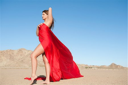 Full length of a young woman wrapped in red cloth on arid landscape Stock Photo - Premium Royalty-Free, Code: 693-06379199