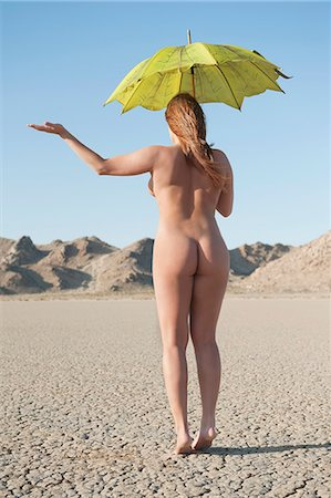 Back view of a naked woman holding umbrella with hand held out on barren landscape Stock Photo - Premium Royalty-Free, Code: 693-06379204