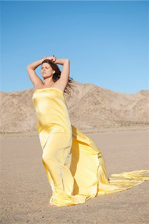 Young woman wrapped in yellow cloth on arid landscape Stock Photo - Premium Royalty-Free, Code: 693-06379200