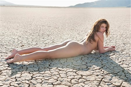 Naked young woman lying on cracked arid landscape Stock Photo - Premium Royalty-Free, Code: 693-06379201