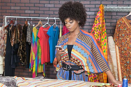 Attractive African American female fashion designer using cell phone Stock Photo - Premium Royalty-Free, Code: 693-06379258
