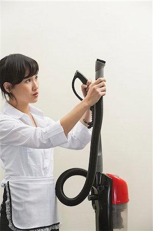 Female housekeeper holding vacuum cleaner pipe against gray background Stock Photo - Premium Royalty-Free, Code: 693-06379356