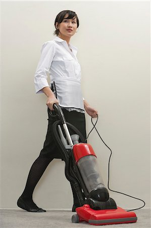 Full length of young female housekeeper vacuuming Stock Photo - Premium Royalty-Free, Code: 693-06379357