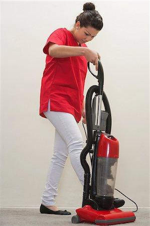 Full length of female housekeeper using vacuum cleaner Stock Photo - Premium Royalty-Free, Code: 693-06379358