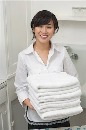 Portrait of young female housekeeper holding clean white folded towels Stock Photo - Premium Royalty-Free, Code: 693-06379368