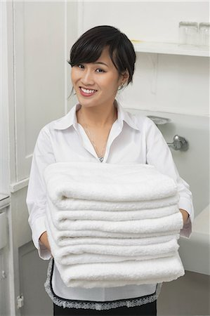 Portrait of beautiful housemaid holding white towels Stock Photo - Premium Royalty-Free, Code: 693-06379369