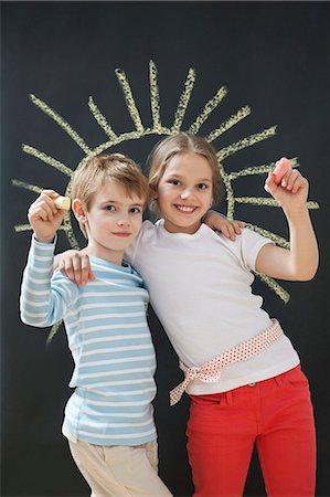 Portrait of happy siblings holding chalks against blackboard Stock Photo - Premium Royalty-Free, Code: 693-06379381