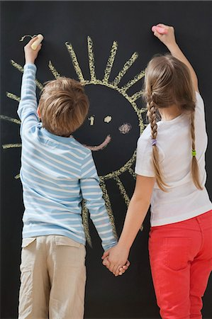 drawing - Back view of siblings drawing sun on blackboard while holding hands Stock Photo - Premium Royalty-Free, Code: 693-06379382