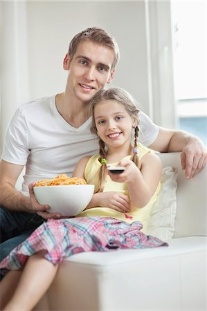 Portrait of father and daughter watching TV with bowl full of wheel shape snack pellets Stock Photo - Premium Royalty-Free, Code: 693-06379394