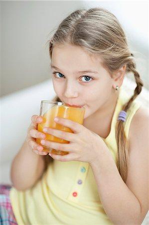 Portrait of little girl drinking orange juice Stock Photo - Premium Royalty-Free, Code: 693-06379395
