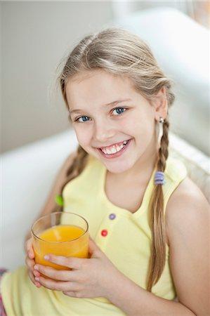 Portrait of girl drinking orange juice Stock Photo - Premium Royalty-Free, Code: 693-06379396