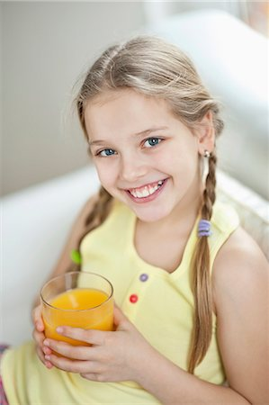 Portrait of girl drinking orange juice Stock Photo - Premium Royalty-Free, Code: 693-06379396