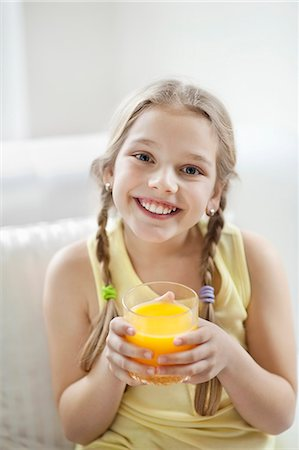 Portrait of happy young girl drinking orange juice Stock Photo - Premium Royalty-Free, Code: 693-06379397