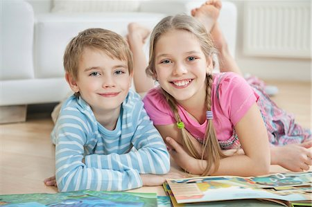 Portrait of happy brother and sister with story books while lying on floor Stock Photo - Premium Royalty-Free, Code: 693-06379399