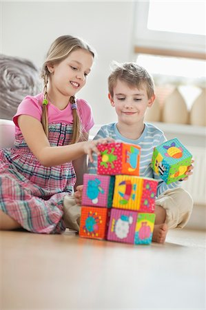 Children stacking blocks while sitting on floor Stock Photo - Premium Royalty-Free, Code: 693-06379404