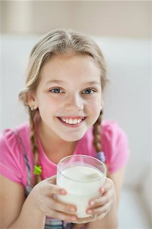 Portrait of happy young girl drinking milk Stock Photo - Premium Royalty-Free, Code: 693-06379406