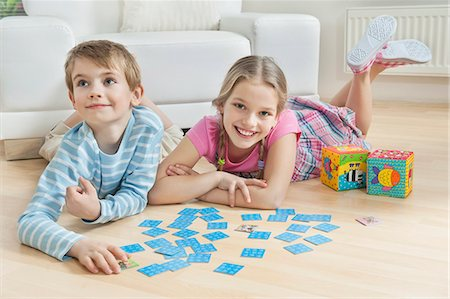 Portrait of a girl and little brother lying on floor with cards Stock Photo - Premium Royalty-Free, Code: 693-06379402