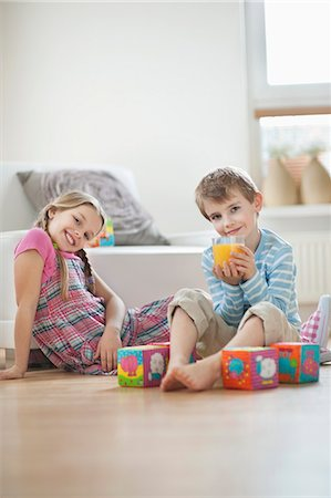 Portrait of young boy drinking orange juice while sitting with sister on floor Stock Photo - Premium Royalty-Free, Code: 693-06379403