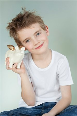 Boy holding a piggy bank over gray background Stock Photo - Premium Royalty-Free, Code: 693-06379419