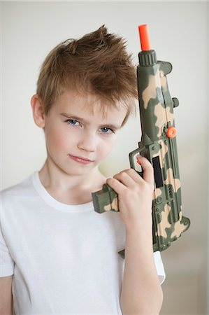 spike - Side view of a young boy holding toy gun Stock Photo - Premium Royalty-Free, Code: 693-06379412