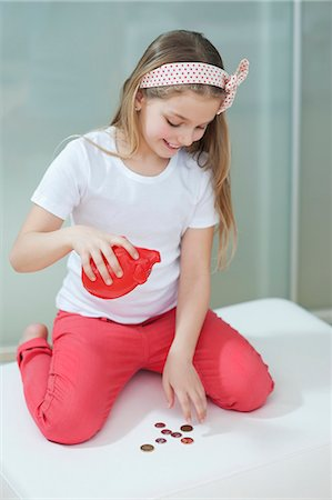 Young girl with piggy bank counting coins on bed Stock Photo - Premium Royalty-Free, Code: 693-06379427