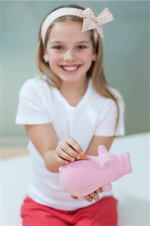 Portrait of a happy girl putting coin in piggy bank Stock Photo - Premium Royalty-Free, Code: 693-06379428