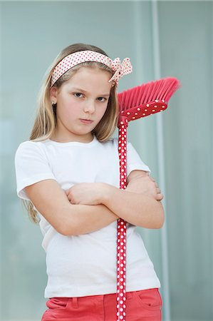 Portrait of an angry girl with broom Stock Photo - Premium Royalty-Free, Code: 693-06379429