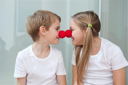 Happy young siblings in white tshirts rubbing clown noses against each other Stock Photo - Premium Royalty-Free, Code: 693-06379434