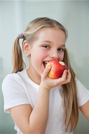 Portrait of happy young girl eating an apple over gray background Stock Photo - Premium Royalty-Free, Code: 693-06379436