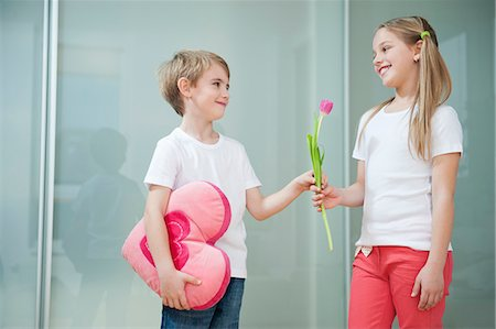 Little boy with heart shape cushion giving flower to girl Stock Photo - Premium Royalty-Free, Code: 693-06379439