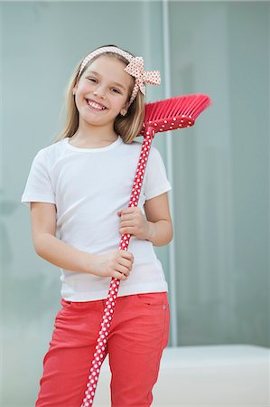 Portrait of a happy young girl with broom Stock Photo - Premium Royalty-Free, Code: 693-06379430