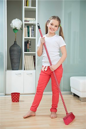 Portrait of a young girl sweeping floor with broom Stock Photo - Premium Royalty-Free, Code: 693-06379432