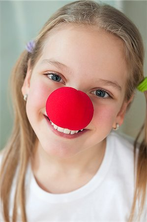 preteen  smile  one  alone - Close-up portrait of a happy girl with red clown nose Stock Photo - Premium Royalty-Free, Code: 693-06379433