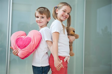 Boy and girl with heart shape cushion and teddy bear holding hands while standing back to back Stock Photo - Premium Royalty-Free, Code: 693-06379440