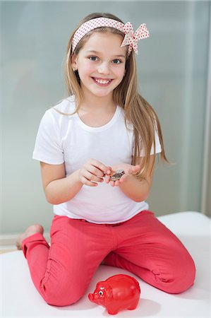 Portrait of girl with piggy bank and coins sitting in bed Stock Photo - Premium Royalty-Free, Code: 693-06379452