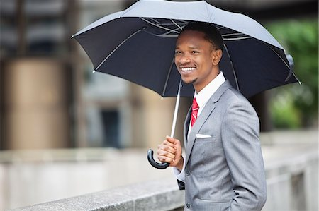 Happy African American businessman holding umbrella Stock Photo - Premium Royalty-Free, Code: 693-06379467