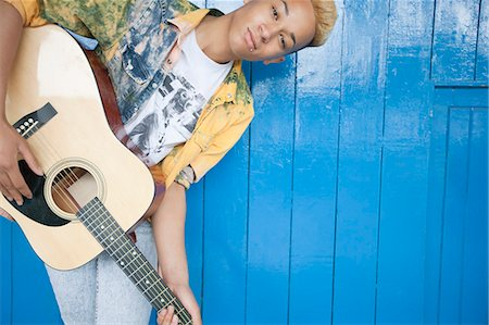 Portrait of a teenage boy playing guitar against wood paneled wall Stock Photo - Premium Royalty-Free, Code: 693-06379489