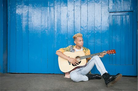 Trendy teenage boy playing guitar as he sits against wood paneled wall Stock Photo - Premium Royalty-Free, Code: 693-06379490